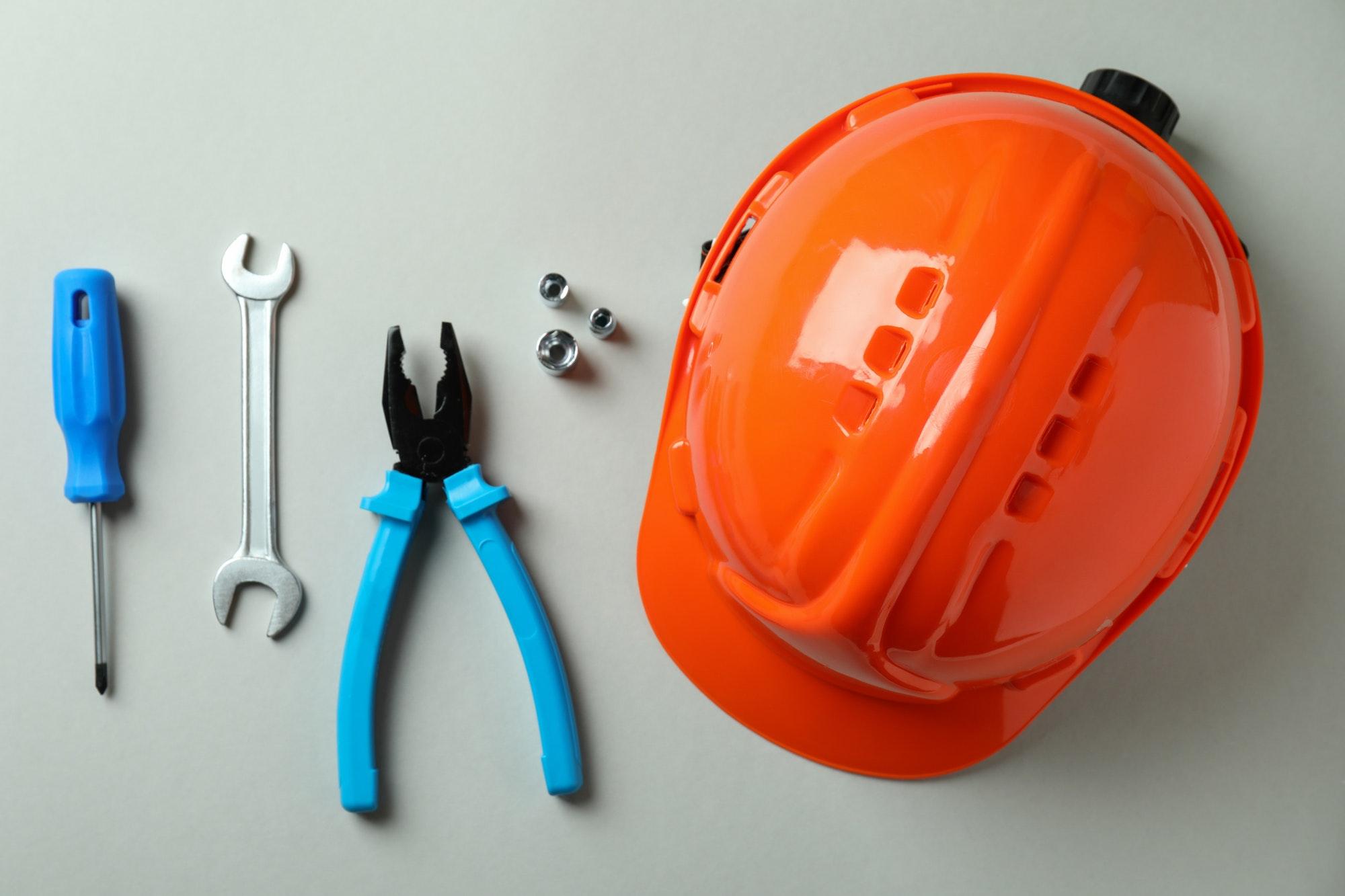 Hard hat and working tools on light gray background